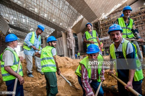 Egyptian construction workers excavate soil outside the entrance of the Grand Egyptian Museum in Giza on the southwestern outskirts of the capital...
