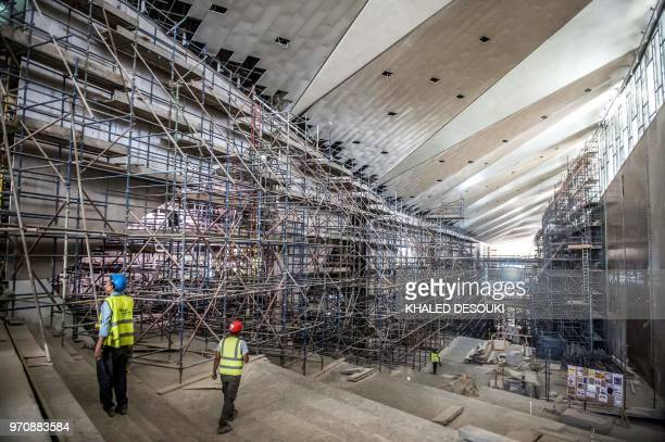 Egyptian construction workers walk at the construction site of the Grand Egyptian Museum in Giza on the southwestern outskirts of the capital Cairo...