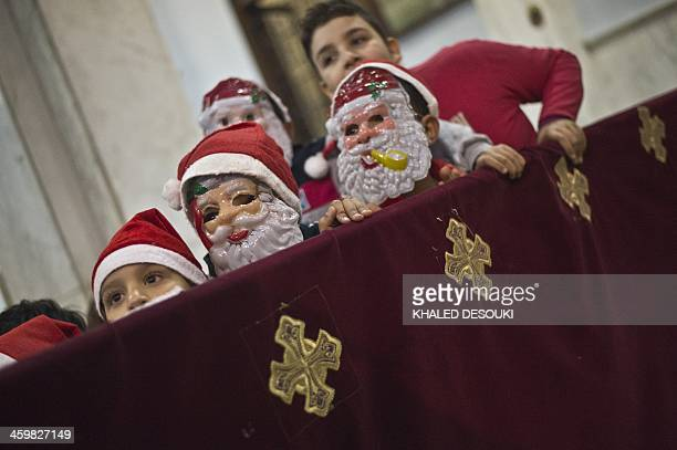 Egyptian Coptic children dressed in Santa Claus attend the New Year mass service at the Virgin Mary Coptic Christian church in Cairo's working class...