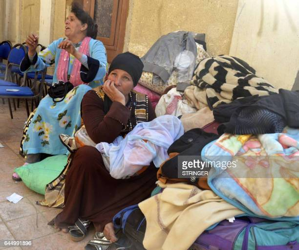 Egyptian Coptic Christians sit in the courtyard of the Evangelical Church in the Suez Canal city of Ismailiya on February 24 upon arriving to take...
