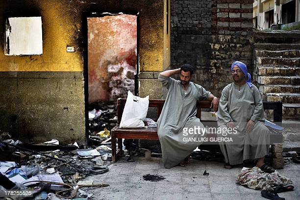 Egyptian Coptic Christians sit on a bench near debris that remain in the courtyard of Amba Moussa Coptic church after it was vandalized and torched...