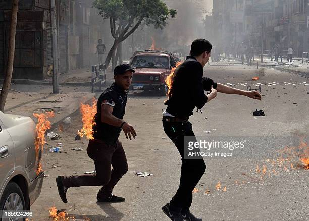 Egyptian Coptic Christians try to put out their burning clothes after they were attacked by unidentified individuals outside the cathedral in the...