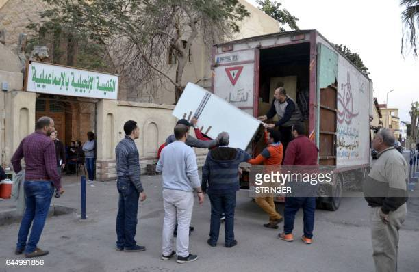 Egyptian Coptic Christians unload their belongings from a truck as they arrive to take refuge at the Evangelical Church in the Suez Canal city of...