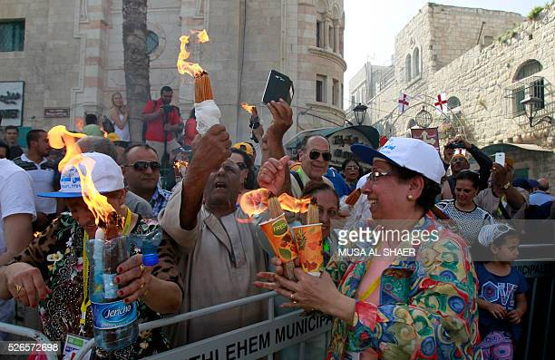 """Egyptian Coptic Christians watch a live broadcast of the """"Holy Fire"""" ceremony in the Church of the Holy Sepulchre in Jerusalem as they stand outside..."""