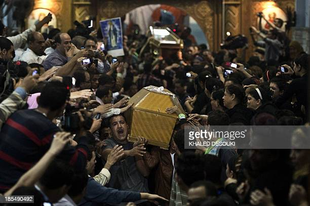 Egyptian Copts carry four coffins down the aisle of the Virgin Mary Coptic Christian church in Cairo's working class neighbourhood of AlWarrak on...
