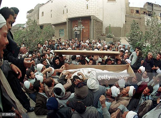 Egyptian Copts gather 04 January 1999 around the coffin of one of the 20 victims of the 02 January 2000 sectarian clashes in the southern Egyptian...