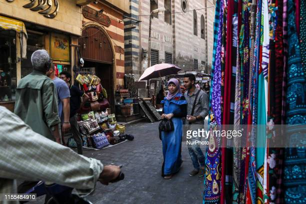 Egyptian couple walk on the street of Khan el Khalil district, Il Cairo, Egypt on 11 July 2019.