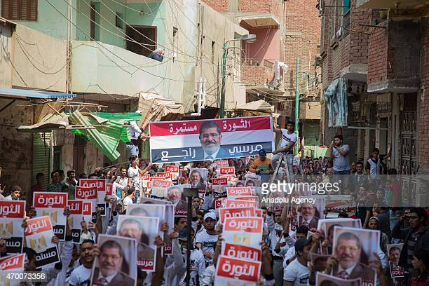 Egyptian demonstrators who call themselves as 'Anti-Coup demonstrators', carry posters of Mohamed Morsi during an anti-government protest in Giza,...