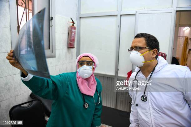 Egyptian doctors check a patient's lung X-ray at the infectious diseases unit of the Imbaba hospital in the capital Cairo, on April 19 during the...