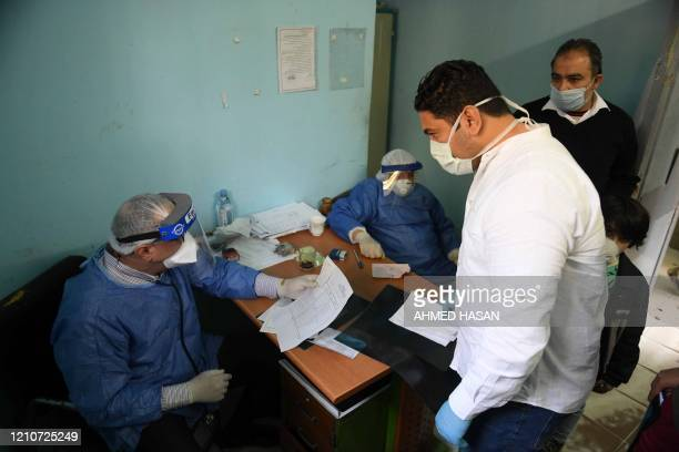 Egyptian doctors receive patients at the infectious diseases unit of the Imbaba hospital in the capital Cairo, on April 19 during the novel...