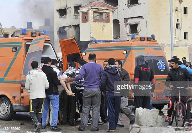 Egyptian emergency personnel move a victim into an ambulance following a car bomb explosion that targeted a police station in North Sinai's...