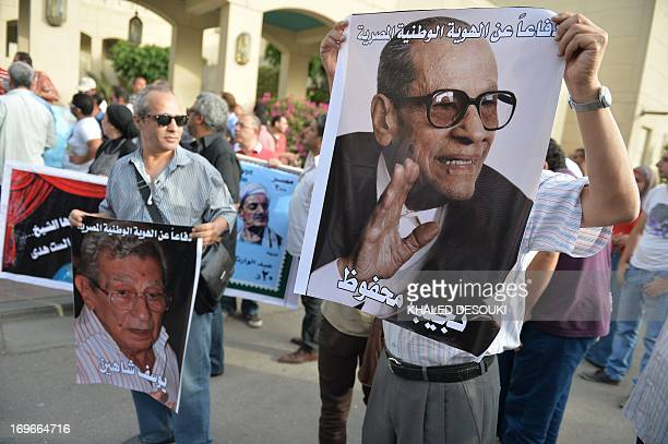 Egyptian employees of the Cairo Opera House and opponents of Egypt's Islamist president Mohamed Morsi hold a portrait of the late Nobel Prize for...