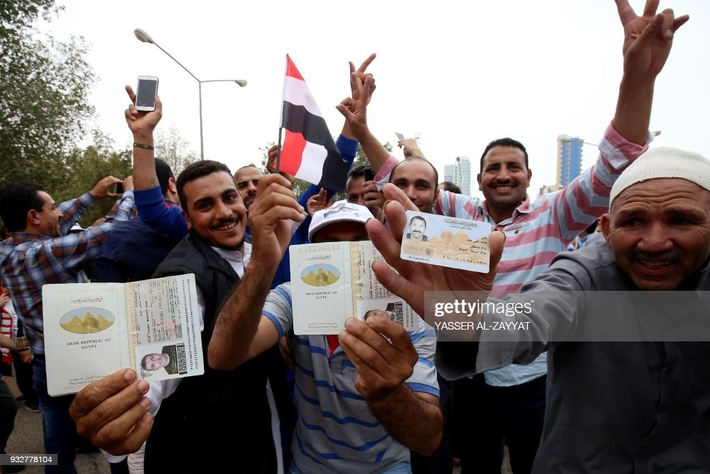 Egyptian expatriates living in Kuwait show their passports