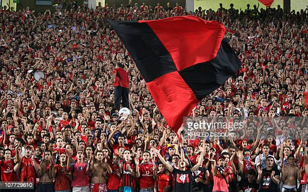 Egyptian fans of AlAhly club cheer before their team's African Champions League group B football match against Algeria's Kabylie club in Cairo on...