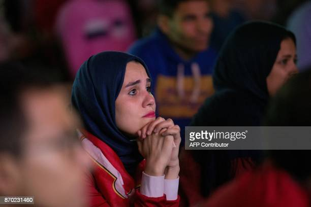 Egyptian football fans react as they watch from the outskirts of Cairo the CAF Champions League final football match between Egypt's AlAhly and...