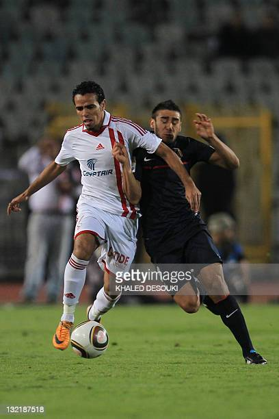 Egyptian footballer Hazem Emam of Zamalek club competes with Eduardo Salvio of Atletico Madrid during their friendly football match in Cairo on...