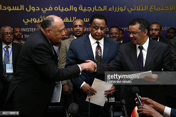 Egyptian Foreign Minister Sameh Shoukri shakes the hand of Ethiopian Foreign Minister Tedros Adhanom in the presence of Sudanese Foreign Minister...