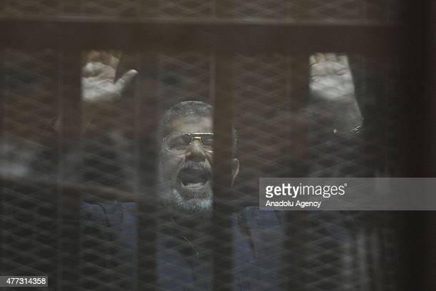 Egyptian former President Mohamed Morsi stands behind the bars during his trial in Cairo on June 16 2015 An Egyptian court on Tuesday sentenced...