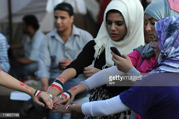 Egyptian girls take a photograph of their hands painted with their national flag as protesters gather in Cairo's landmark Tahrir Square on July 18 to...