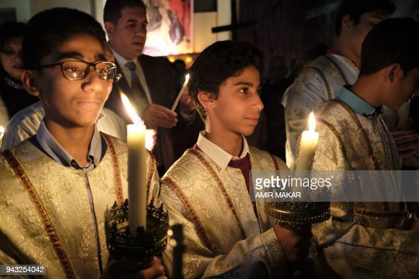 Egyptian Greek Orthodox acolytes hold candles during the midnight Easter Saturday vigil at the Greek Orthodox Church of the Archangels in Cairo's...