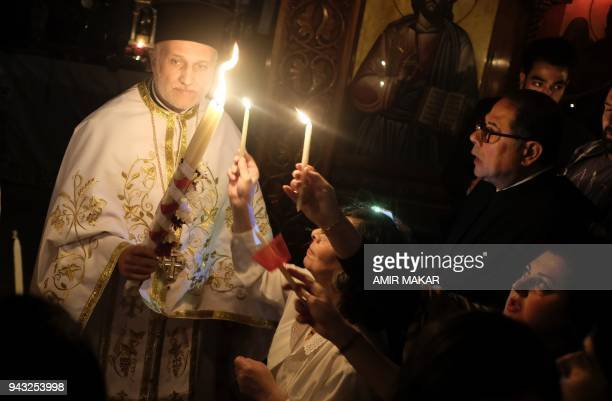 Egyptian Greek Orthodox priests extend their candles to light up for worshippers during the midnight Easter Saturday vigil at the Greek Orthodox...
