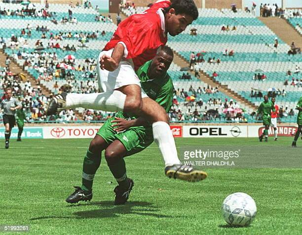 Egyptian Hazem Emam leaps for a kick and snatches the ball from a Zambian midfielder during Four Nations Cup finals in Johannesburg 26 November Egypt...