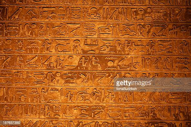 egyptian hieroglyphics on a beige stone - egyptian culture stock photos and pictures