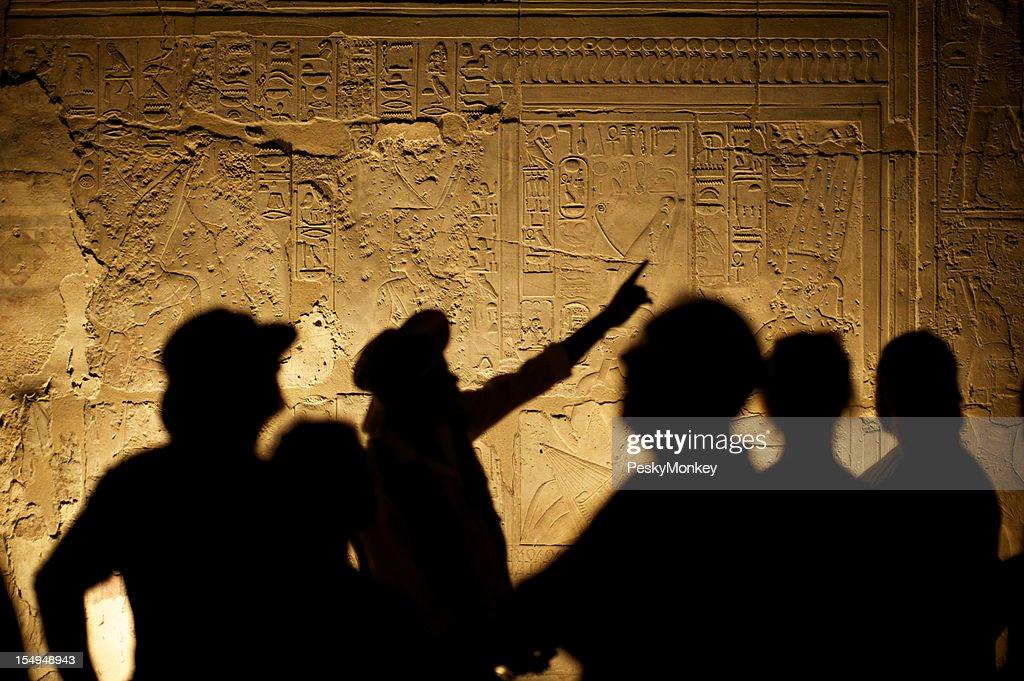 Egyptian Hieroglyphs with Tourist Archeologist Silhouettes : Stock Photo