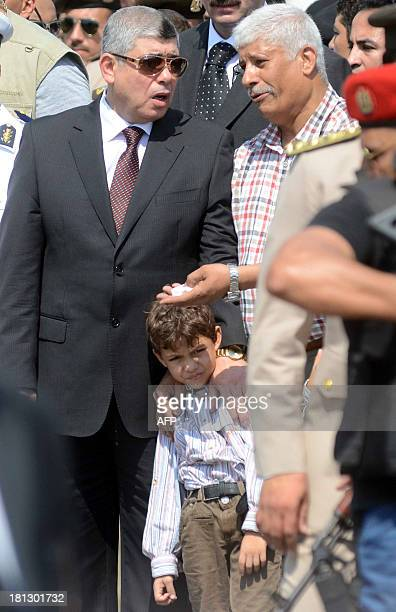 Egyptian Interior Minister Mohammed Ibrahim stands next to the son of Giza security chief Nabil Farrag fiveyearold Ahmad during his father's funeral...
