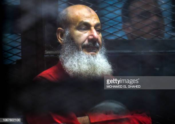 Egyptian islamist cleric and TV preacher Safwat Hegazi sits behind bars in a glass cage during a trial for him and other members of the now-banned...