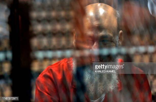 Egyptian Islamist preacher Safwat Hegazy is seen behind bars during a verdict and sentencing session of a retrial for him and other Brotherhood...