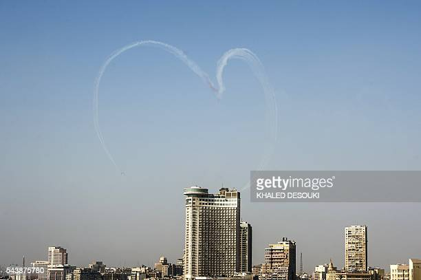 TOPSHOT Egyptian jet fighters trail smoke as they fly over Tahrir Square in the capital Cairo on June 30 2016 during a celebration of the third...