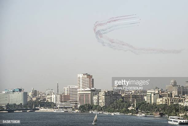 Egyptian jet fighters trail smoke as they fly over Tahrir Square in the capital Cairo on June 30 2016 during a celebration of the third anniversary...