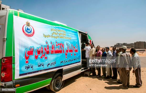 Egyptian labourers line up for an examination checkup for Hepatitis C at a construction site in Egypt's new administrative capital some 40 kms east...
