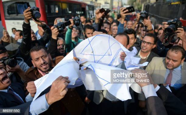 Egyptian lawyers burn a makeshift paper Israeli flag as they chant slogans during a protest outside the Bar Association headquarters in downtown...