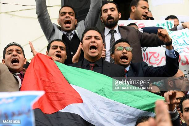 Egyptian lawyers wave a Palestinian flag as they chant slogans during a protest outside the Bar Association headquarters in downtown Cairo on...