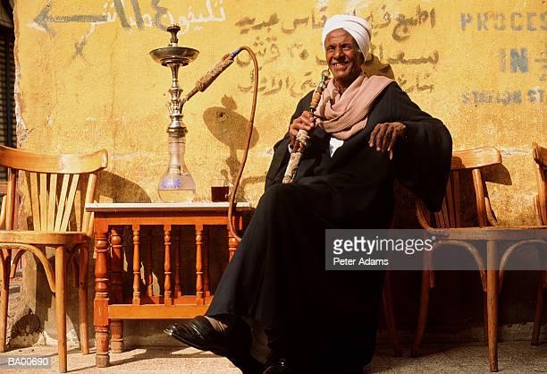 Egyptian man drinking tea and smoking pipe