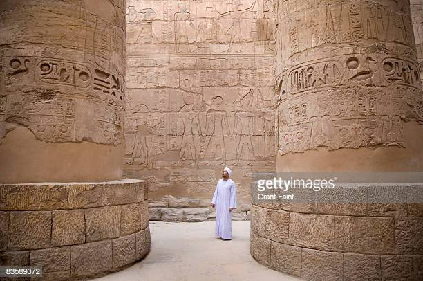 egyptian man standing in karnak temple columns - egypt stock pictures, royalty-free photos & images