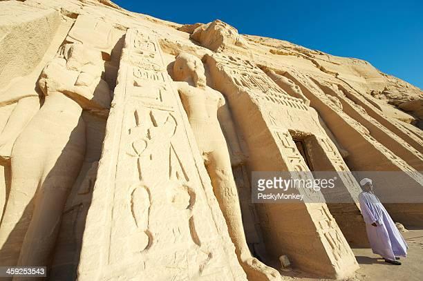 Ägyptische Mann geht in front kleine Tempel von Abu Simbel