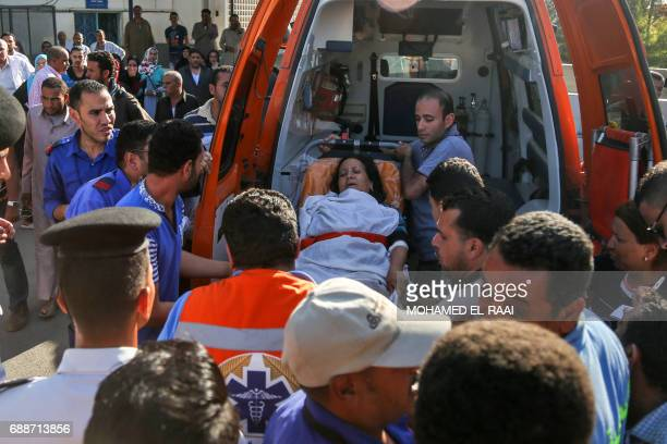 Egyptian medics unload a wounded woman from the back on an ambulance outside a hospital in Cairo's northern suburb of Shubra on May 26 following an...