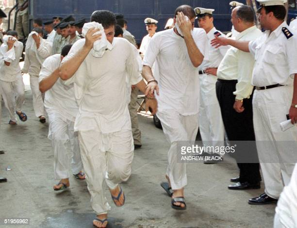 Egyptian men accused of having gay sex cover their faces as they walk into a Cairo court 18 July 2001 The trial of the 52 Egyptians opened amid...