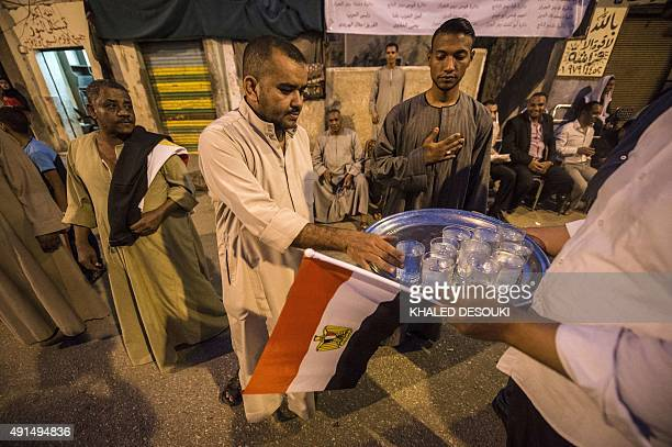GABRIEL Egyptian men are offered water during a campaign meeting of the main 'For The Love of Egypt' coalition ahead of the parliamentary elections...