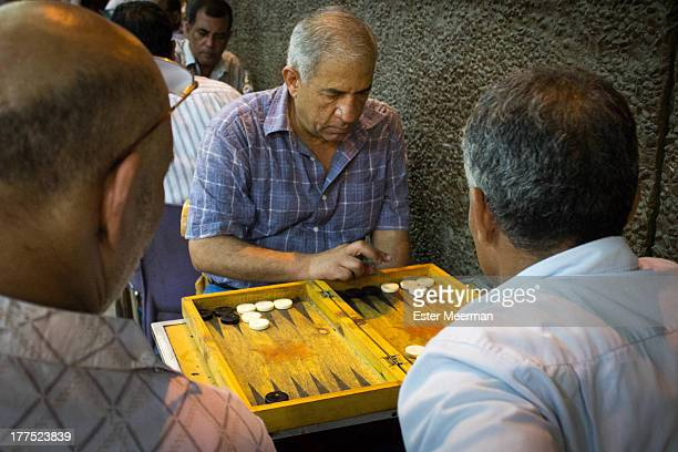 Egyptian men are playing a game of backgammon, a very popular activity in one of the many outdoor cafes on the streets of Cairo.