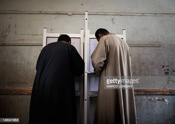 Egyptian men fill their ballots at a polling station in the Coptic Mensheit Nasser district in Cairo on May 23 as Egyptians vote in historic...
