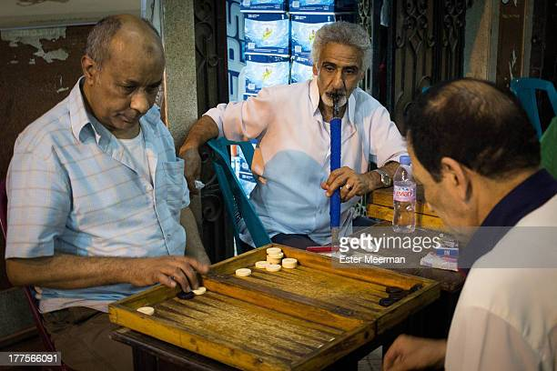 Egyptian men playing a game of backgammon in Cairo, Egypt. Backgammon - locally known as tawla - is a popular pastime in the many outdoor cafes.