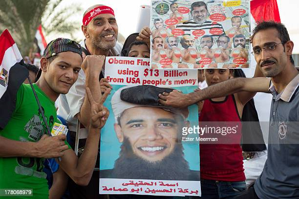Egyptian men pose on Tahrir square in Cairo, with banners against the American president Barack Obama, om the 26th of July 2013, the day army general...