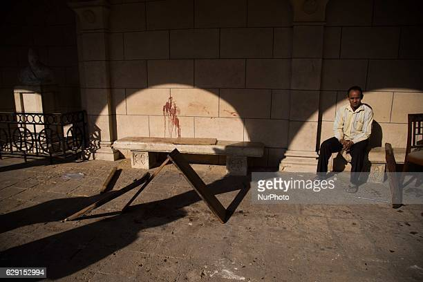 Egyptian men sit at the scene of a bomb explosion that targeted the Saint Peter and Saint Paul Coptic Orthodox Church on December 11 in Cairo's...