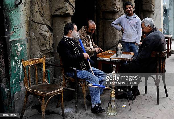 Egyptian men smoke the traditional waterpipe and play backgammon at a cafe in downtown Cairo on December 30 2011 AFP PHOTO / FILIPPO MONTEFORTE