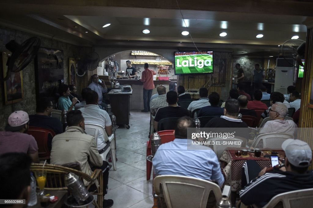 TOPSHOT - Egyptian men watch the Clasico football game between Real Madrid and Barcelona FC at a cafe in Cairo on May 6, 2018.