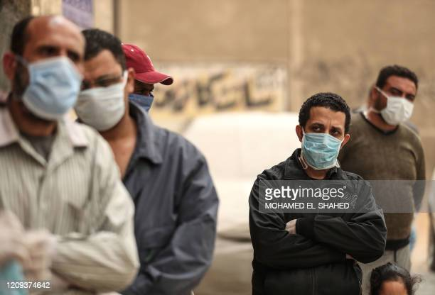 Egyptian men wearing masks wait outside a centre of non-governmental organisation Egyptian Food Bank to receive cartons with foodstuffs on April 05...